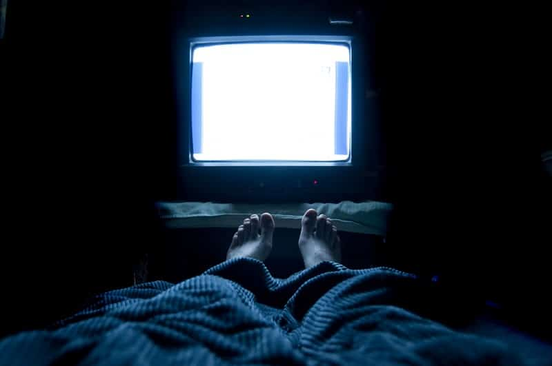 Person watches TV at night in his bed with his feet sticking up out of the blankets