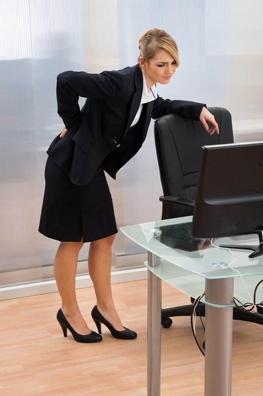 Young Businesswoman In Office Leaning On Office Chair And Having Backpain